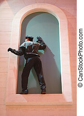 Second Story Man - A mannequin posed in the window of a pink...