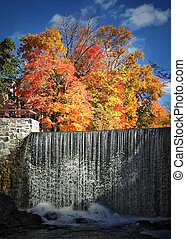 Bright waterfall with red and orange autumn trees