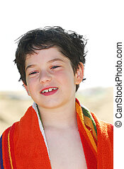 Boy in a towel - Young boy wrapped in a towel on a beach...