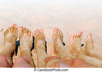 Sandy feet - Row of childrens feet on a beach covered in...
