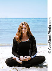 Meditation at the beach - A woman in deep meditation at the...