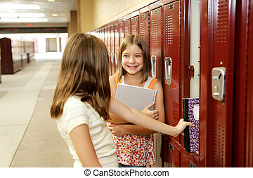 Gossip by Lockers - Middle school girls gossiping at their...