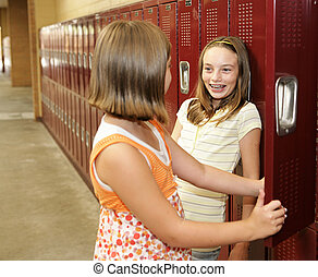 Locker Chitchat - Two middle school students chatting at...