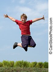 boy jumps - A little boy jumps with sky at background