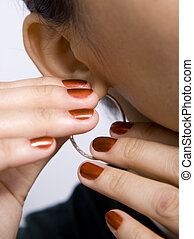 Putting on earrings - Nice girl putting on earring with red...