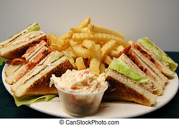turkey club sandwich on a plate with fries and coleslaw