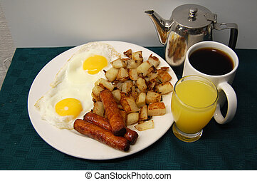 breakfast table - a plate of eggs, sausage, homefries, tea,...