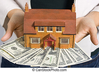 House and money - A person holding a miniature house and...