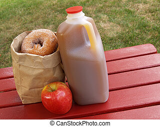 apple cider and donuts - apple cider, an apple and a bag of...