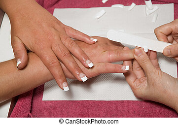Manicurist installing nails - Manicurist shaping fake nails