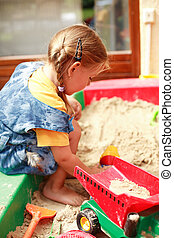 Child playing in sandbox - Little child playing in sandbox...
