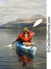 Kayaking on Loch Lomond - Female kayaker on Loch Lomond with...