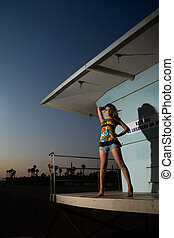 Woman on lifeguard building - Attractive woman standing on a...