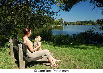 Lady with dog at lakeside - Lady with dog resting at...