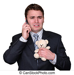 Young Businessman Crying on Cell Phone, clutching Teddy...