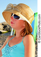 Teenage girl wearing hat and sunglasses relaxing on a beach