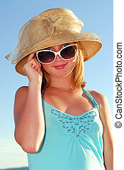 Teenage girl wearing hat and sunglasses on a summer beach