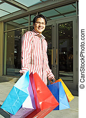 Shopping - A happy young man carrying shopping bags at an...