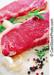 Raw steak - Two raw new york steaks on cutting board with...
