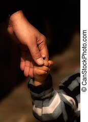 Growing up - Image shows a hand of an adult holding the hand...