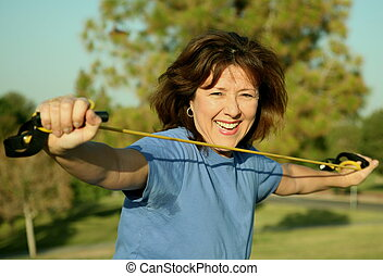 Woman exercising outside with resistance band