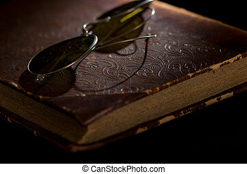 glasses on an old book - An old worn accounting book and...