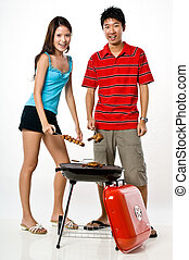 Couple and BBQ - A young man and young woman standing...