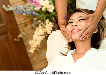 Face Massage - A young Asian woman having a face massage in...