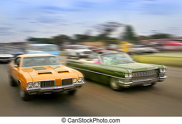 Muscle Cars - Orange and green color muscle cars cruising on...