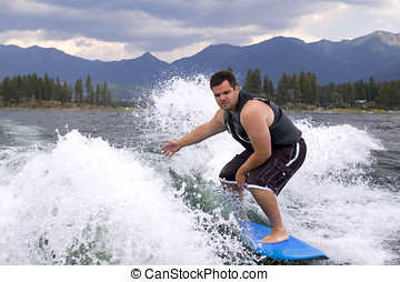 Wake surfing - Man surfing with a blue board on the wake of...