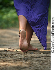 woman legs - The girl with barefooted legs goes on a forest
