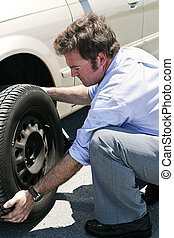 Flat Tire - Dirty Job - A businessman changing a flat tire...
