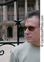 Watching Carefully - Man in front of an ironwork gate...