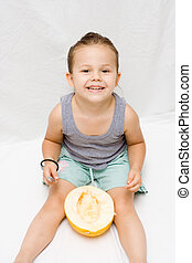 Melon - little cute girl eating fresh melon summer time
