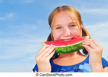 Girl with watermelon - Young girl biting into a slice of...