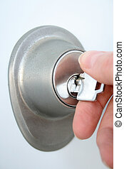 Hand unlocking the door with a key - Woman\\\'s hand...