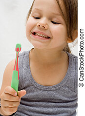 Teeth brushing - the little cute girl brushing her teeth