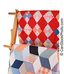 Two Quilts On A Wood Rack - Detail view of two multicolor...