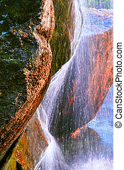 Rock and water - Water flowing down over big granite rock