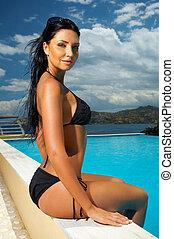 Black Bikini Girl - Beautiful young Sexy woman sitting in...