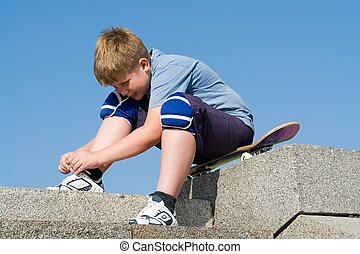 boy ties the shoe-lace sitting on the skateboard
