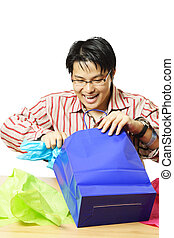 Shopping gifts - An isolated shot of a young man opening...