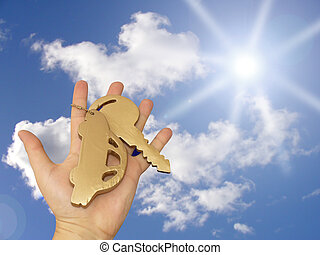 Car ownership concept - Car golden key in hand on blue sky...