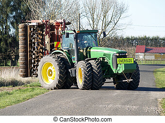 Work Over - A large tractor leaving the field with the...