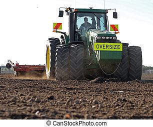 Large Tractor Preparing Soil - A large tractor cultivating a...