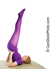 Senior Yoga - Shoulder Stand - A fit senior woman smiling as...