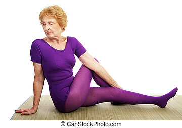 Senior Yoga - Spinal Twist - A senior woman in her seventies...