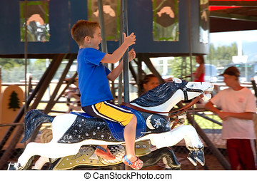 Carousel Rider - Boy having a great time on a carousel.
