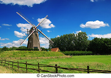 Vintage windmill - An old windmill against a blue vibrant...