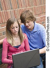 Teens - Young teenagers a boy and a girl working on a laptop...